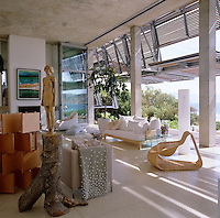 The main living area with a view out through hydraulic shutters to the terrace has a floor of terrazzo slabs and the sculpted figure is by Egon Tania