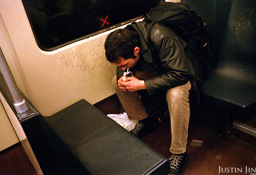 A drug addict smokes crack on the last metro to Bijlmer, a poor inner city area in Amsterdam. .Picture taken 2005 by Justin Jin