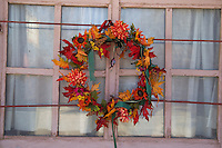 Fall colors on a wreath nailed to a window frame