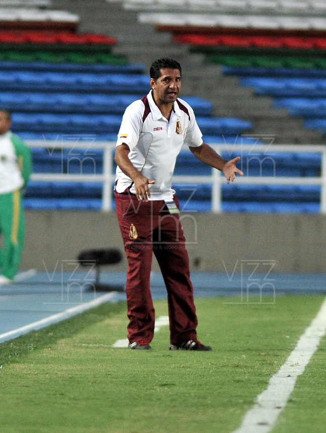 CALI - COLOMBIA -02-04-2014: Carlos Castro, tecnico Deportes Tolima da instrucciones a los jugadores durante  partido Deportivo Cali y Deportes Tolima por la fecha 16 de la Liga Postobon I 2014 en el estadio Pascual Guerrero de la ciudad de Cali.   / Carlos Castro, coach of Deportes Tolima gives instructions to the players during a match between Deportivo Cali and Alianza Petrolera for the date 16th of the Liga Postobon I 2014 at the Pascual Guerrero stadium in Cali city. Photo: VizzorImage / Luis Ramirez / Staff.