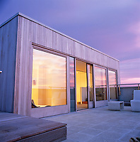 The garden room is clad in iroko wood and opens on to the roof terrace