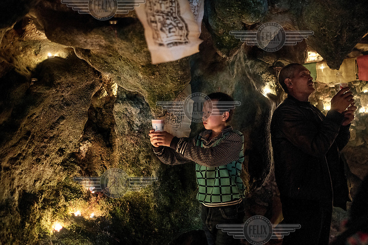 Local Nu, Lisu and Tibetan people celebrate the Fairy Festival and arrival of spring by collecting water dropping from stalactites in a sacred cave and making an offering at a Tibetan Buddhist altar.