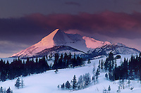 798600012 winter sunrise paints snow covered antler peak in pink alpenglow as storm clouds clear over yellowstone national park in wyoming