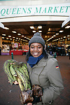 Sarah Akoto holding  a plantain  - Sarah is a  Ghanaian stall holder and market trader  in Queens Market, Upton Park East London, which is being  threatened with redevelopment.