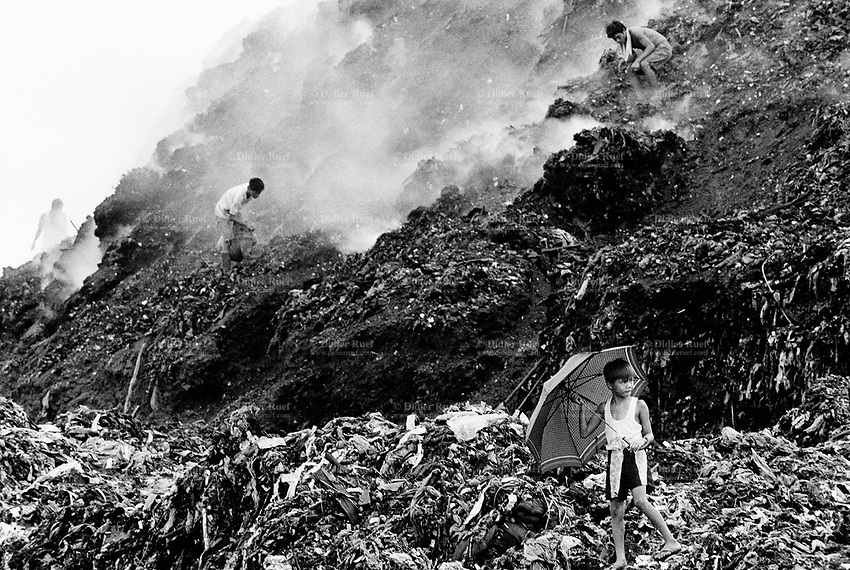 Philippines. Luzon Region. Manila. Tondo area. Smokey mountain is a rubbish dump. Life on a garbage heap. A boy with an umbrella walks near a group of scavengers on dumpsite. They collect various rubbish items in order to resell them as recycled products. © 1992 Didier Ruef .