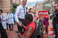 NYC Public Advocate and mayoral candidate Bill de Blasio greets wheelchair-bound Francisco Gonzalez at his endorsement in New York by the Committee of Interns and Residents on Wednesday, August 14, 2013. De Blasio has currently taken the lead in the Quinnipiac University Poll with 30 percent. Christine Quinn follows with 24 percent, then William Thompson at 22 percent and Anthony Weiner with 10 percent. John Lui and Sal Albanese are in the single digits. (© Richard B. Levine)