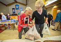 STAFF PHOTO JASON IVESTER --11/13/2014--<br /> Fran Cranmer (cq) (right) of Rogers helps Mary Michael of Rogers carry her bags to her car from the food pantry on Thursday, Nov. 13, 2014, inside Grace United Methodist Church in Rogers.