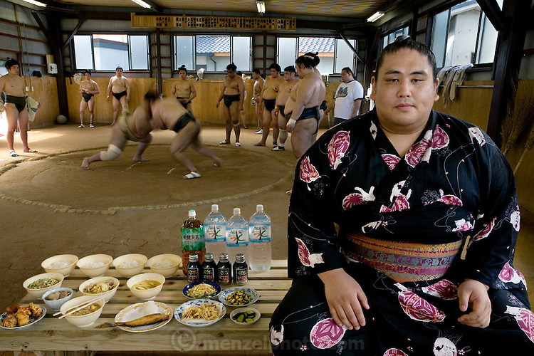 """Takeuchi Masato, a professional sumo wrestler whose ring name is Miyabiyama (meaning """"Graceful Mountain""""), with his day's worth of food in the team's practice ring in Nagoya, Japan. (From the book What I Eat: Around the World in 80 Diets.) MODEL RELEASED."""