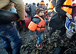 A refugee boy stands on a beach near Molyvos, on the Greek island of Lesbos, on November 2, 2015, as he and his family disembark from a rubber raft that brought them from Turkey. The boat was provided by Turkish traffickers to whom the refugees paid huge sums to arrive in Greece.