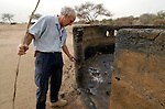 Brian Martin, the head of programs for the ACT-Caritas Darfur Emergency Response, inspects the remnants of a house in the burned out village of Um Seifa, one of hundreds of burned villages in Sudan's Darfur region, the product of violence by government military forces and Arab militias against an insurgent force and the civilian population of the area.
