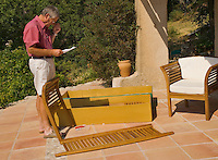 Man assembles flat packed garden furniture on the terrace of his house.Reading the assembly instructions.  Model released.