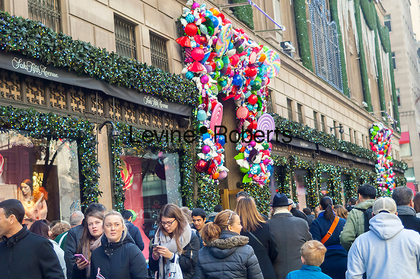 Crowds of shoppers in front of the holiday decorations on Saks Fifth Avenue in Midtown Manhattan in New York on Sunday, November 27, 2016. The National Retail Federation reported that 43.8% of consumers shopped online during the four-day weekend.  (© Richard B. Levine)