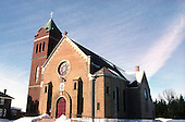 Catholic Church in Notre-Dame-des-Lourdes in winter with blue sky.  Red brick church