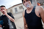 "At right, ""El Mongo"" and his cousin smoke marijuana outside their home in Ciudad Juarez."