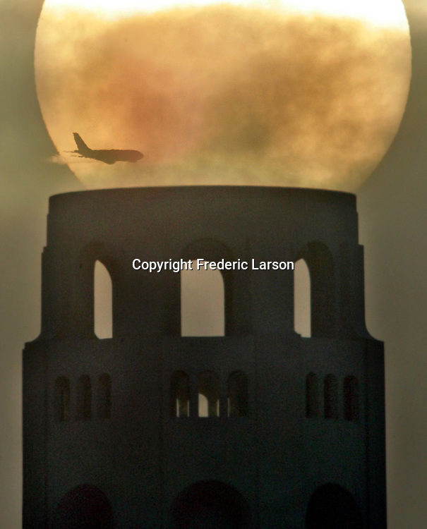 A jet zoom through its way through San Francisco's morning while Coit Tower made a perfect place for the sunrise to pause.