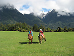 Chile, Lake Country: People riding horses at Peulla in a meadow in the Andes..Photo #: ch612-263..Photo copyright Lee Foster www.fostertravel.com, lee@fostertravel.com, 510-549-2202.
