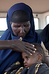 MATHAHALIBAH, KENYA - JULY 4: Mohammedek Siyad, 21 months old, is held by his grandmother seated in a Save the Children veihle after visiting a Save the Children outreach site in the location on July 4, 2011 in Mathahalibah, Kenya. The boy was referred to the hospital in nearby Habaswein. The team examined about thirty children, among them several severely malnourished. Mohammedek's grandmother Habiba Sahal came with him to the outreach site to receive some food and medicine. His mother left three months ago with their remaining livestock. Forced away due to the sever drought in the area. She is expected back when rain falls again. Mohammedek is now being cared by his grandmother. Two successive poor rains, entrenched poverty and lack of investment in affected areas have pushed millions of people into a fight for survival in the Horn of Africa. This is the driest this area have been since sixty years. (Photo by Per-Anders Pettersson)