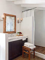 A simple, fresh, white bathroom with a decked floor to the walk in shower and marble-topped wash stand