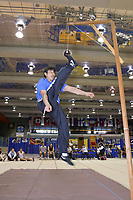 One foot high kick at the World Eskimo Indian Olympics held annually in July, Fairbanks, Alaska. The high kick event requires the athlete to jump off the floor using both feet, kick a suspended object with one foot, and land on the floor using that same foot demonstrating balance to the floor officials.