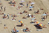 Spain. Ibiza in the Balearic islands. Ibiza. Tourists take a rest, sunbathe and sleep on a sandy beach in Ibiza City. Mediterranean sea. © 1999 Didier Ruef