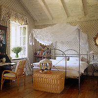 A white lace canopy is draped over the metal four-poster bed that dominates this attic bedroom