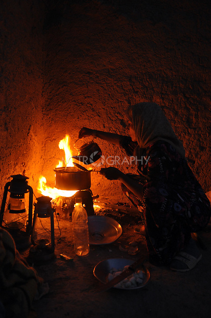 DOWDA, IRAQ:  Rehan Ibrahim cooks duck over a gas fire...Iraqi forces decimated the Dowda area in Germian during the 1988 Anfal genocidal campaign against the Kurds.  Daily life continues is this extremely harsh part of Iraq...Photo by Aram Karim/Metrography