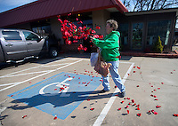 NWA Democrat-Gazette/JASON IVESTER<br /> Jamie Hollingsworth, delivery driver, tosses rose petals Monday, Feb. 13, 2017, on the parking lot at Springdale Flower Shop. Rusty Eldridge, owner, estimates the shop will sell between 3,000 and 4,000 roses for the Valentine's Day holiday.