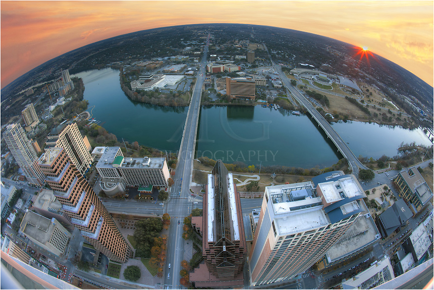 With a fisheye lense, this image captures  the sun setting west of Austin, Texas, and the Texas Hill Country. Town Lake (Ladybird Lake) winds through the downtown area. and from I-35 to the east to Lamar Bridge to to the west, with Congress and 1st Street Bridges in between, this panorama of Austin shows the view from 54 stories high.