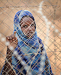 A newly arrived Somali girl watches through a razor wire fence at activities inside the reception center of the Dagahaley refugee camp, part of the Dadaab refugee complex in northeastern Kenya.
