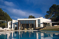 The glass doors of the house open onto a large swimming pool which sparkles in the sunlight