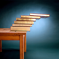 STABLE EQUILIBRIUM: STACK OF BOOKS ON TABLE EDGE<br /> Relating Center of Gravity to Area of Support<br /> The maximum distance from the table edge to the center of mass of the topmost book is the sum of the successive overhangs. By stacking enough books it is possible to make the stable pile lie as far off the table as desired.