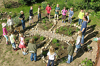 Schulgarten, Anlage eines Schmetterlingsgarten, Garten der Grundschule Nusse wird als Projektarbeit von einer 1. Klasse gestaltet, Beete werden in Form eines Schmetterlings angelegt und mit für Nektarliebende Falter wichtigen Blumen bepflanzt, Kinder und Lehrerin bilden einen Kreis um ihr Werk, Gartenarbeit