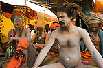 A naked Holy Man, sitting in lotus position with other Sadhu at the Kumbh Mela Festival in Allahabad,  India