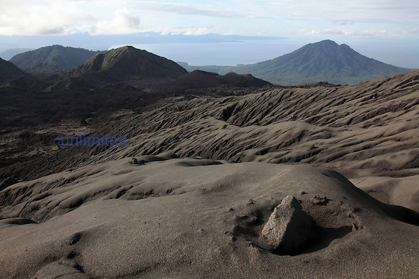 Flank of Dukono Volcano with volcanic bomb in impact crater in foreground, Halmahera, Indonesia.