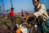 A cyclist carries up drinking water in Bokapahari village in Jharia, outside of Dhanbad in Jharkhand, India.   Photo: Sanjit Das/Panos