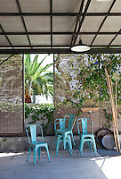A set of distressed bistro chairs is grouped on a covered terrace beside the swimming pool