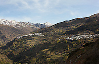 Capileira, (left) and Bubion (right), gorge of the Poqueira river, Alpujarra, Andalucia, Southern Spain, with snow-capped mountains in the distance. Moorish influence is seen in the distinctive cubic architecture of the Sierra Nevada's Alpujarra region, reminiscent of Berber architecture in Morocco's Atlas Mountains. Photograph by Manuel Cohen.