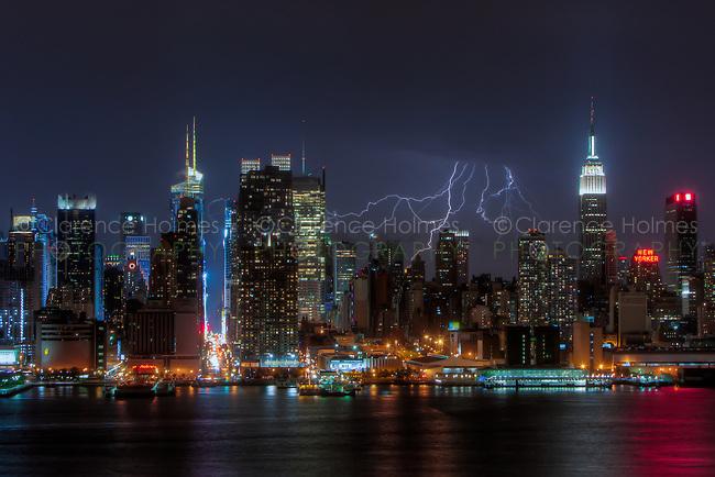 Lightning bolts illuminate the night sky behind the skyline of New York City during a summer thunderstorm on Sunday, July 15, 2012.