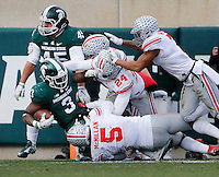 Michigan State Spartans running back LJ Scott (3) backs his way toward the endzone past Ohio State Buckeyes linebacker Raekwon McMillan (5) and safety Malik Hooker (24) during the fourth quarter of the NCAA football game at Spartan Stadium in East Lansing, Mich. on Nov. 19, 2016. Scott scored on the next play, but Michigan State failed to convert the 2-point conversion. Ohio State won 17-16. (Adam Cairns / The Columbus Dispatch)