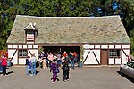 Mill Neck, New York, U.S. 12th October 2013. People visit the Cheese House at the annual Fall Harvest Festival, also known as Apple Fest, which attracts tens of thousands of visitors with its food and more, on the grounds of Mill Neck Manor, an historic Gold Coast estate, during Columbus Day weekend. The Tudor Revival style building of wood and stucco has a slate roof with tiles that are biggest along the bottom and become smaller as they reach the top of the roof, to create an optical illusion that the building is actually bigger than it is. Proceeds benefit the Mill Neck Family of organizations including the Mill Neck Manor School for the Deaf.