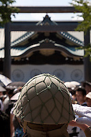 A man in Imperial era soldier`s uniform salutes at Yasukuni Shrine. On August 15th every year people gather at Yasukuni Shrine to commemorate the end of the Pacific War. Notionally a call for remembrance and continued peace it is also a Mecca for right wing nationalist including  the paramilitary Uyoku Dantai. Tokyo, Japan, August 15th 2009