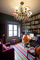 Paolo Bagnara in his book-lined study where the made-to-measure bookshelves and desk have been lacquered a deep aubergine colour