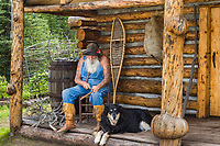 D. C. Smitty (Smitty) poses as a sourdough at his rustic log cabin, Glennallen, Alaska.