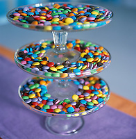 An antique tiered-glass sweetmeats dish displays multi-coloured Smarties
