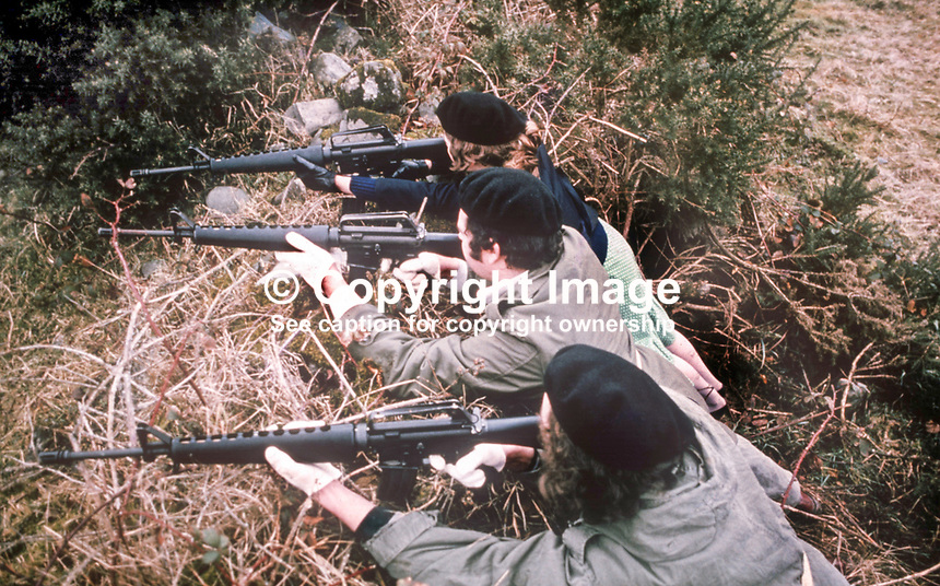 This republican press release photograph claims to be of a Provisional IRA border unit on manoeuvres in Co Fermanagh, N Ireland, February 1977.  The men and women volunteers are seen using Armalite rifles.<br />
