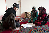 BIARA, IRAQ: Abit al-Jabar helps his two nieces with their arabic studies during a rare trip back to his village...The Biara Madrassa--a religious school--is located high up in the mountainous Kurdish Hawraman region that makes up the Iran/Iraq border. Before 2003 the region was home to a fundamentalist Islamic group called Ansar al-Islam who used the school as a base. The Unites States military attacked the area and the madrassa numerous times during the 2003 invasion, finally pushing Ansar al-Islam out...Today the madrassa is home to 48 male students from all across Kurdish Iraq. The students leave their families and immerse themselves in their studies and the daily life of Koranic students...Photo by Besaran Tofiq