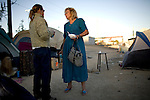 RENO, NV - OCTOBER 6:  Geri Radway, center, chats with a friend as she returns to a tent city for the homeless in downtown Reno, Nevada after working two jobs on October 6, 2008. Radway moved to Reno from Salt Lake City, Utah in search of work, but struggled and only today started a full-time job to complement her part-time job. She hopes to be able to move out of the homeless encampment within a few weeks. The City of Reno set up the tent city when existing shelters became overcrowded as Nevada struggles with one of the highest unemployment rates in the country. (Photo by Max Whittaker/Getty Images)