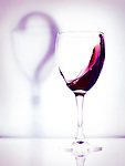 Red wine in a glass and a question mark shadow artistic conceptual photo isolated on white purple background