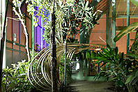 Tropical Rainforest Glasshouse (formerly Le Jardin d'Hiver or Winter Gardens), 1936, Rene Berger, Jardin des Plantes, Museum National d'Histoire Naturelle, Paris, France. Low angle view of the interior of the main Art Deco style entrance at night. The illuminated green foliage of the plants inside the Glasshouse contrasts with the orange and purple glow of the floodlighting against the night sky beyond the windows.
