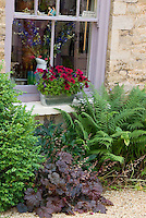 "Pretty garden scene of house window, windowbox of red petunias, underplanted with heuchera Palace Purple in bloom with ferns, vase of larkspur, sign ""We're working in the garden"""